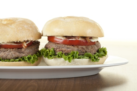 Cropped image of a plate with chicken hamburgers on the wooden table