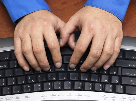 Close-up cropped shot of a human hands typing on black keyboard. Stock Photo - 17149407