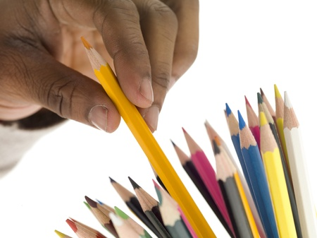 A hand while picking a yellow color pencil on a white background