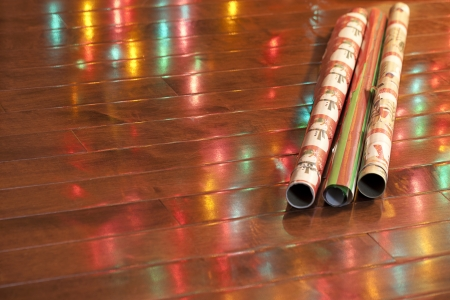 Close-up shot of shiny rolled up wrapping paper with light reflection on wooden plank.