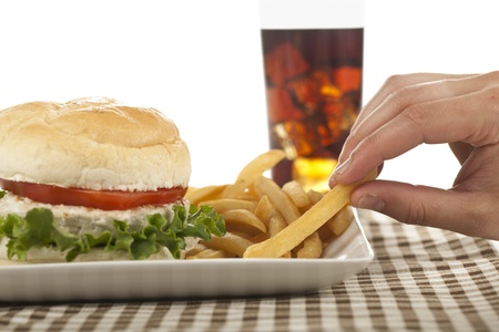 Image of a hand getting fries from the plate with hamburger and soft drink on the background photo