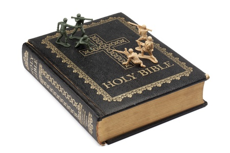 persecution: Soldiers fighting on top of a bible Stock Photo