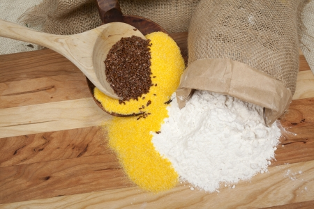 maize flour: Wheat, maize flour and grains spread on a wooden table