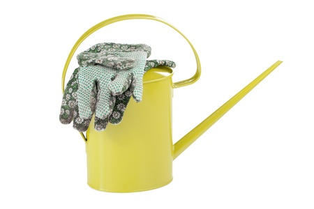 gardening gloves: Close up image of gardening gloves and watering can against white background