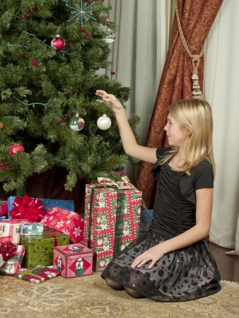 christmas gift: Young girl sitting in front of a Christmas tree while hanging up ornaments. Stock Photo