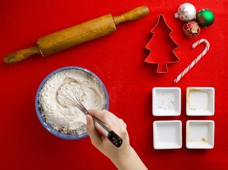 weihnachtskuchen: Close-up Draufsicht einer Person Mischen Mehl mit dem Schneebesen mit Kuchen Zutaten auf rotem Hintergrund.