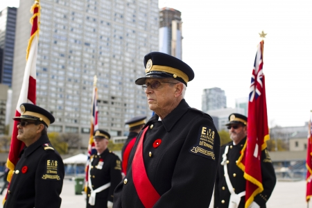 aging american: Image of a senior citizen in military uniform while people standing in background wearing military uniform and holding flag.