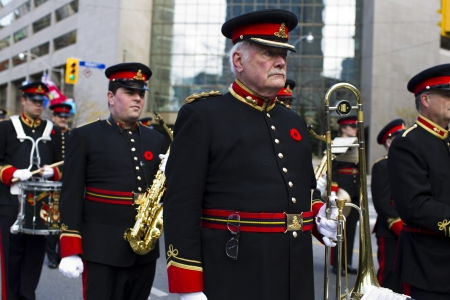 Image of a senior musician of marching band with musical instrument while other musicians with musical instruments in background. photo