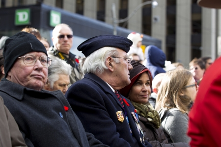 Image of senior citizen in glasses with people in the background.