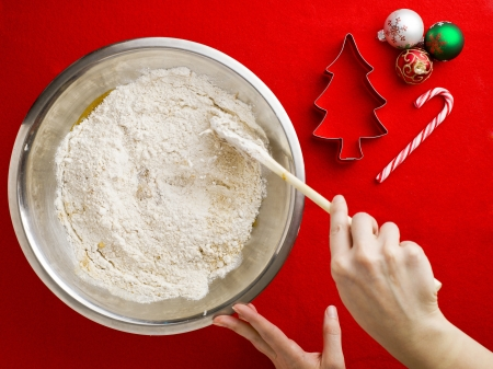 Image of someone mixing flour in chocolate syrup with spatula with cookie cutter and Christmas baubles over red background. photo