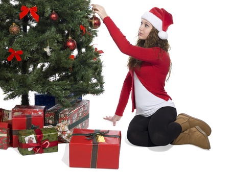 Image of a blonde lady putting a ball decoration in the Christmas tree photo