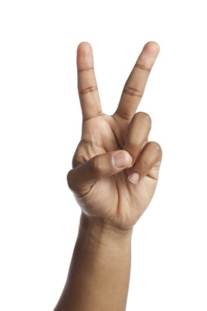 peace sign: Close-up image of human hand with a peace gesture over the white surface