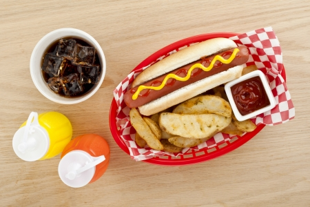 Close up image of hot dog sandwich with fried potato fries with drinks on wooden table Stock Photo - 17148672