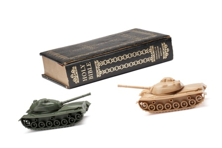 protection of the bible: Close-up image of a military toy tank defending the Holy bible
