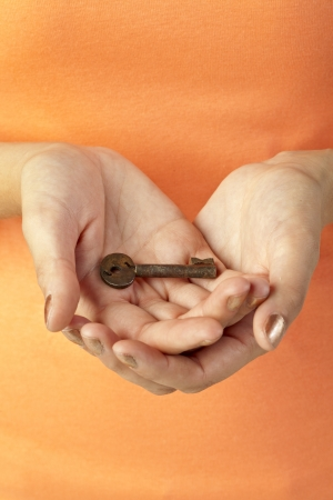 Closed up image of woman' s open palm with a key on top photo