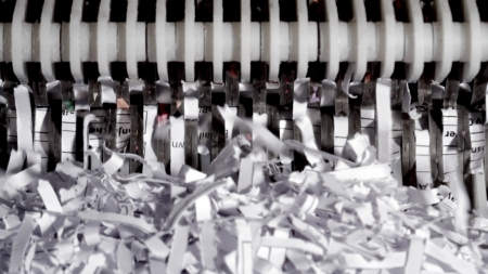 exterminate: Paper shredder with shredded paper in a macro image Stock Photo