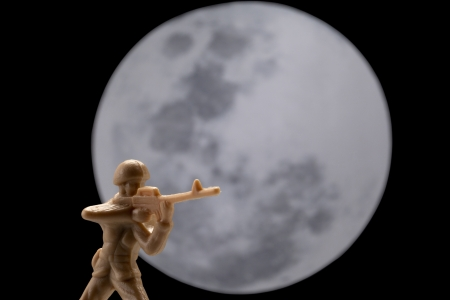 plastic soldier: Image of plastic toy soldier with full moon on the background