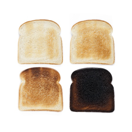 toast: Four slices of bread, at varying stages of toasting. Stock Photo