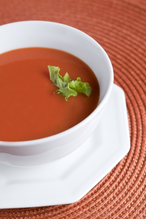 Fresh tomato soup bowl with garnish on a close up image photo