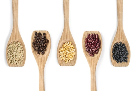 gr: Overhead shot of variety of pulses with coffee beans on wooden spatula.