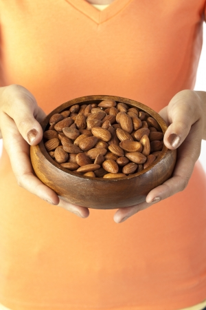 Image of woman holding bowl of almonds Stock Photo