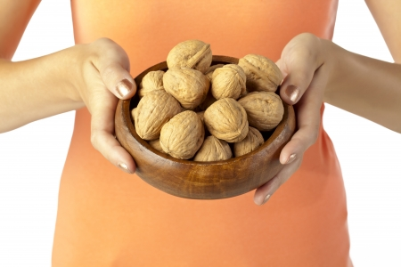 Image of woman holding bowl of walnut against white background Stock Photo - 17152759