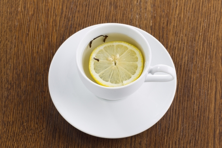 detailed shot: Detailed shot of lime tea with lemon slice on wooden table.