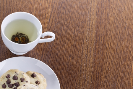 cropped shot: Close-up cropped shot of lime tea with chocolate chip cookies on wooden table. Stock Photo