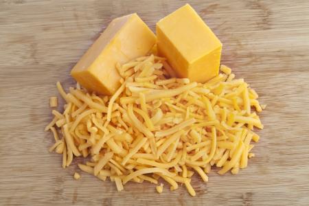 queso cheddar: Queso cheddar rallado en un fondo marr�n