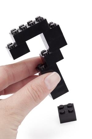 black block: Imagen de primer plano de una mano que sostiene negro lego formando una estructura signo de interrogaci�n