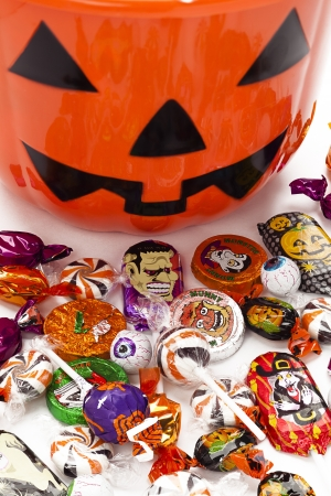 rubbery: Small kids jack o lantern bucket with candies in front.