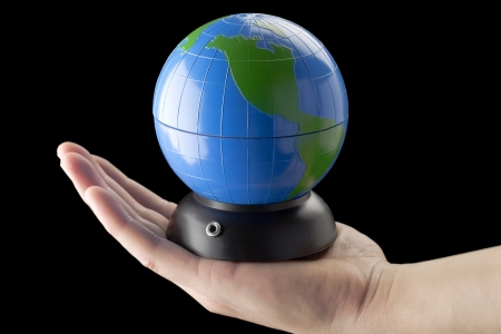 Close-up image of a human palm with globe in a dark background Banco de Imagens