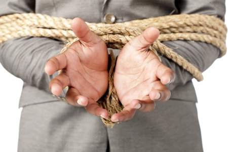 Close up image of businessman hands tied up with rope photo