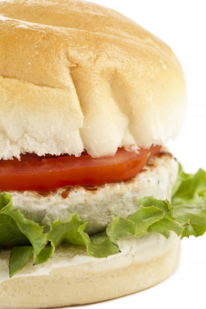 Cropped image of chicken burger with slice tomato and lettuce leaf against the white surface photo