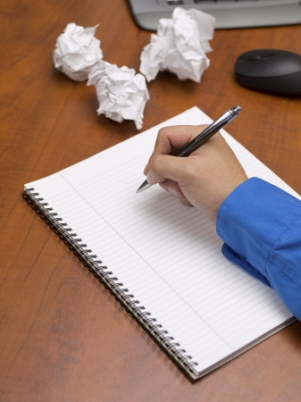 Close-up image of human hand writing on spiral writing pad on wooden office desk with crumpled papers. Stock Photo - 17152938
