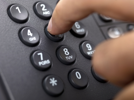 Close-up cropped image of a person dialing landline phone.
