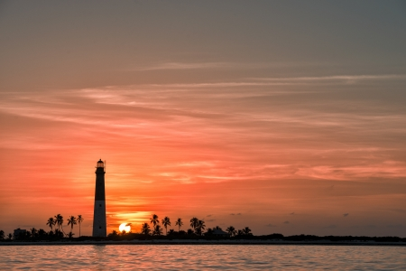 dry tortugas: Distance view of Dry Tortugas lighthouse at dramatic sunset