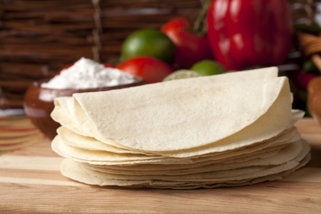 Close-up image of a group of empty tortilla shells with blurred vegetables on the background