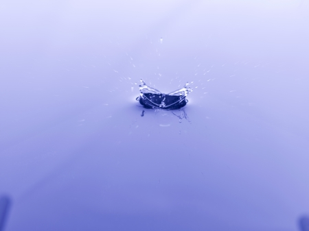 Close-up image of a falling object on blue water creating a splash Stock Photo - 17151924