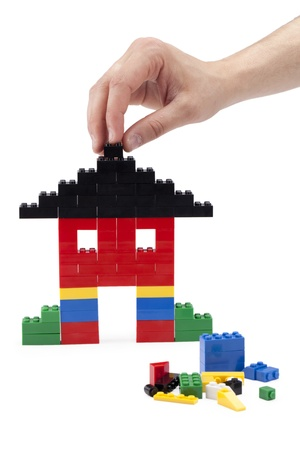 Human hand building a house using plastic LEGO  bricks