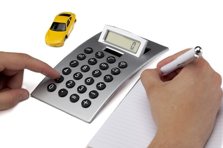 Image of hand writing on the blank paper while computing on the calculator with model car on the side showing a car loan concept
