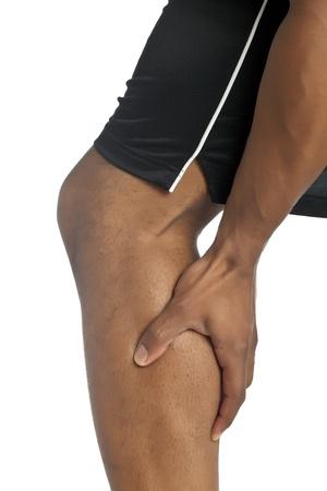 leg calf injury: Closeup shot of a black man touching his aching leg Stock Photo