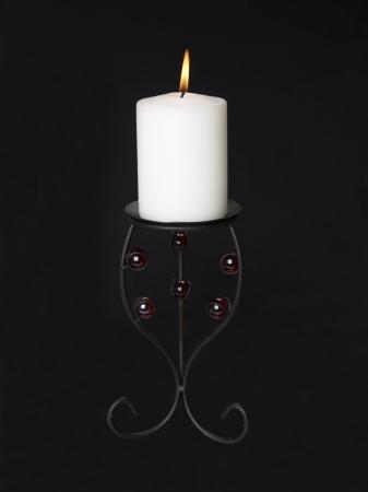 candleholder: Image of lighten candle in black candle holder against black background