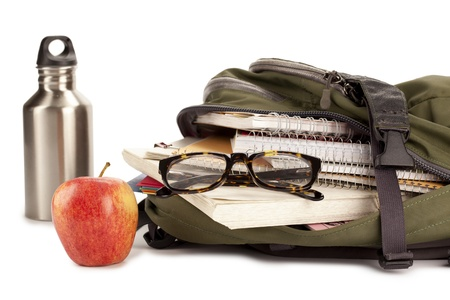 educational tools: School supplies on green backpack with apple beside on a white surface