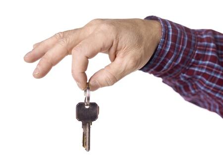 doorkey: Close up immagine della mano umana in possesso di una chiave su sfondo bianco