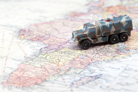 Military armored land vehicle on a blurred map photo