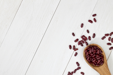 cropped image: Cropped image of a wooden spoon with a spilled red haricot beans on a table