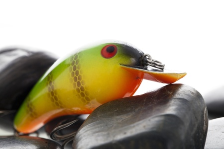 Closed up shot of a plastic fishing lure in stones with a white background photo