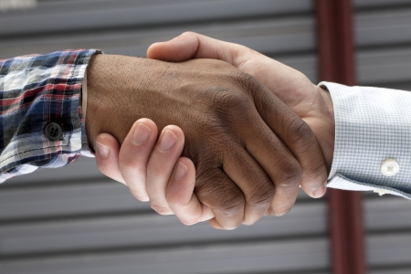 Closed up image of black and white hands doing a handshake Foto de archivo