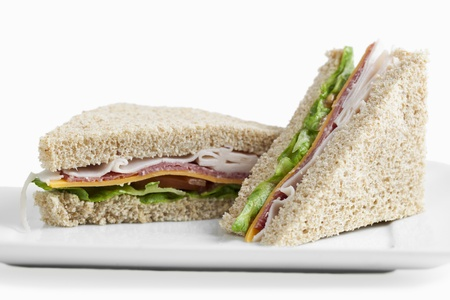 Two club sandwiches served in a plate over white background photo